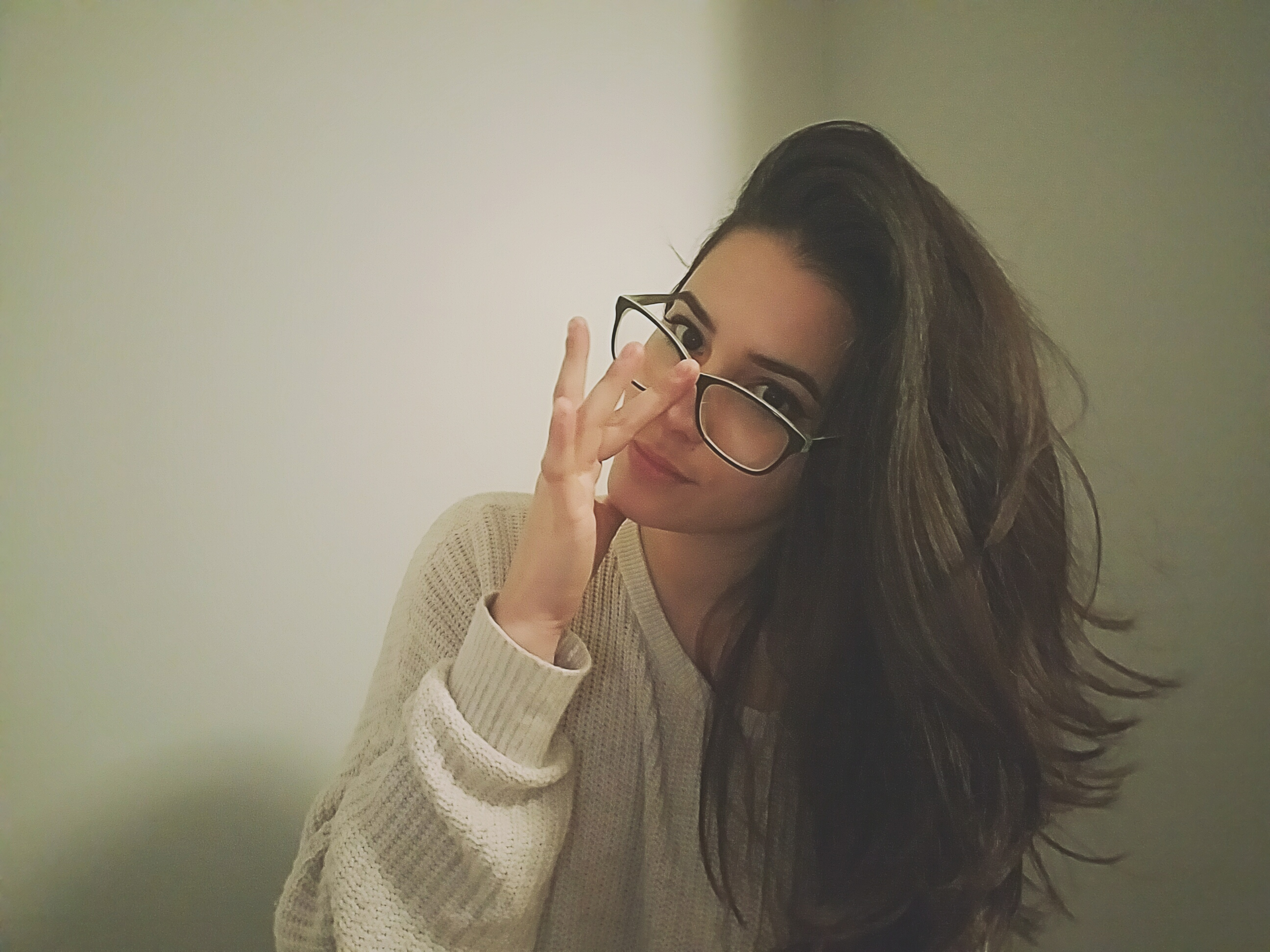 Girl wearing a white knit sweater with long dark hair flipped over to her left, pushing up dark glasses and looking into the camera